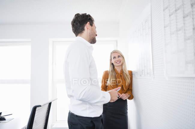 Колеги по роботі з чоловіками і жінками розмовляють в офісі — стокове фото