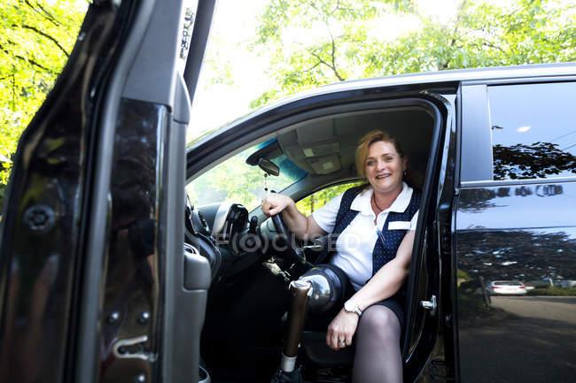 Портрет середині дорослу жінку з протез, сидячи в машині — стокове фото