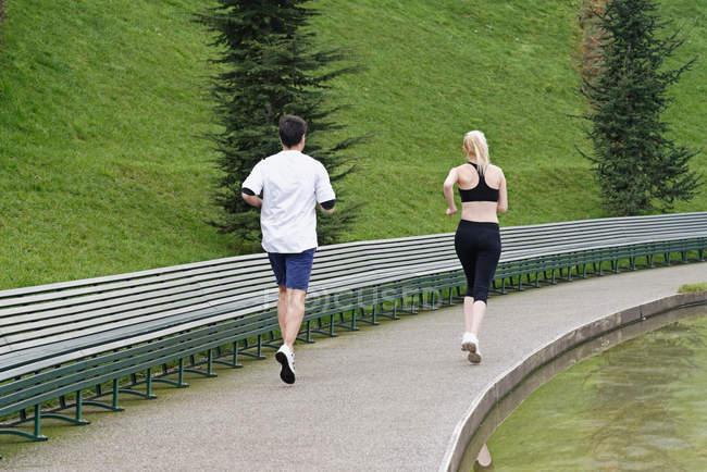 Мужчина и женщина бегут вдоль озера, вид сзади — стоковое фото