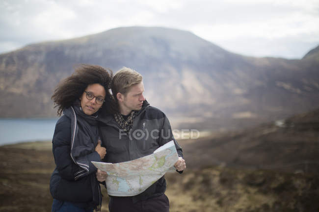 Mid adult couple in mountains with map — Stock Photo