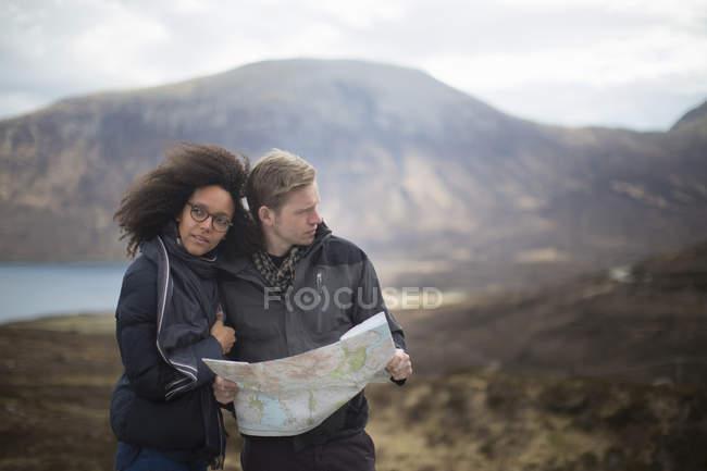 Coppia adulta media in montagna con mappa — Foto stock