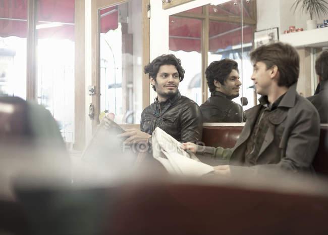 Zwei Männer warten mit Zeitungen im Friseurladen — Stockfoto