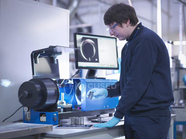 Male engineer testing automotive parts in factory — Stock Photo