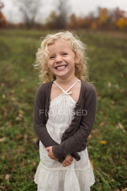 Portrait of preschooler girl smiling outdoors in autumn — Stock Photo