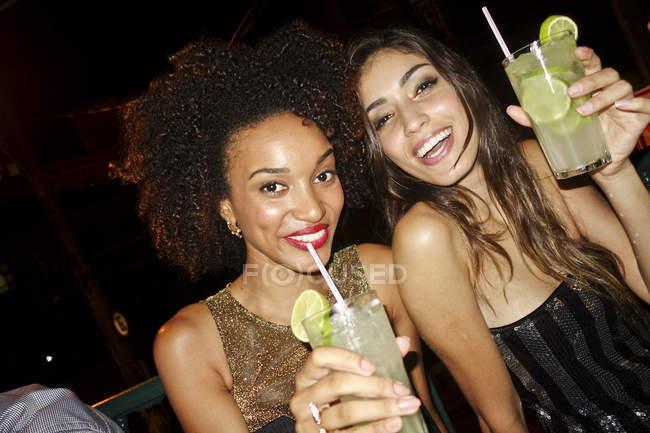 Due giovani donne al bar, che bevono cocktail, guardano la telecamera, sorridono — Foto stock