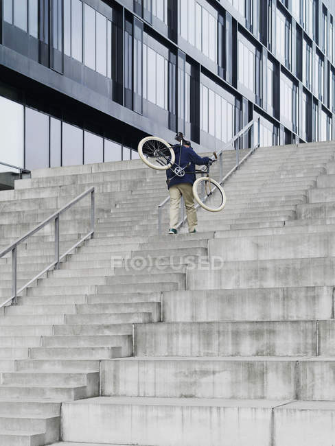 Urban cyclist carrying bicycle ascending stairway — Stock Photo