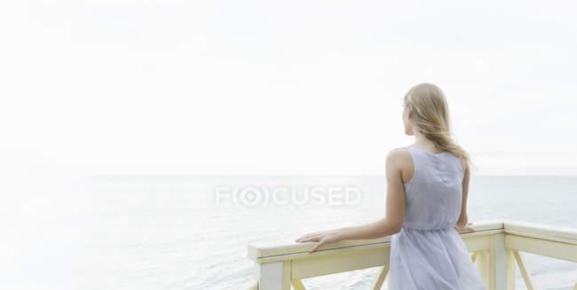 Visão traseira da jovem mulher olhando para o mar a partir da varanda, Miami Beach, Flórida, EUA — Fotografia de Stock