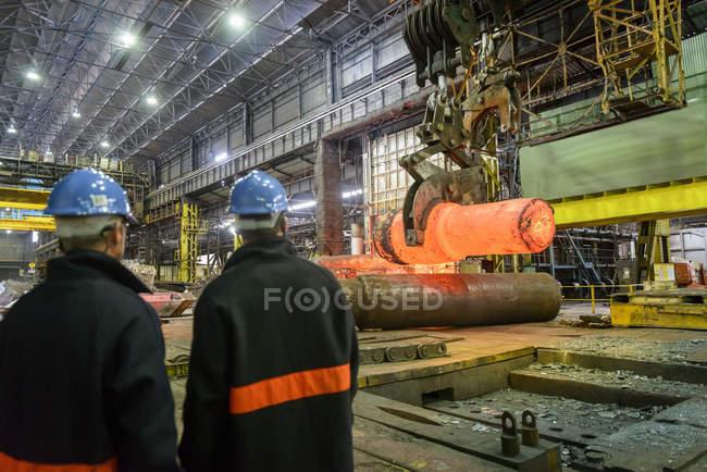 Сталеливарні робітники дивляться гарячий сталевий лиття на крані в сталеливарних роботах — стокове фото
