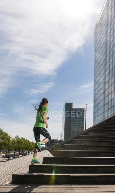 Зрелые женщины бегун, запуск вверх углу города лестница — стоковое фото