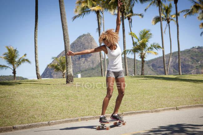 Jeune femme planche à roulettes le long de la chaussée — Photo de stock