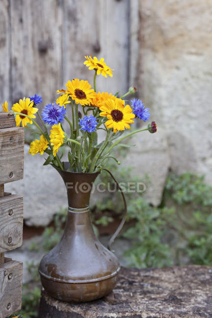 Fresh flowers in metal jug, outdoors — Stock Photo