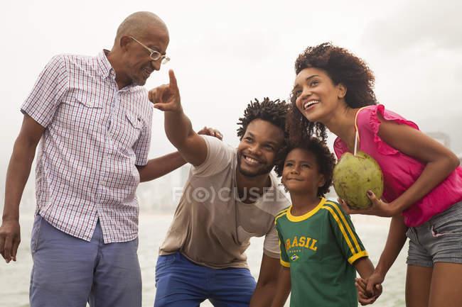 Family of four looking up from Ipanema beach, Rio De Janeiro, Brazil — Stock Photo