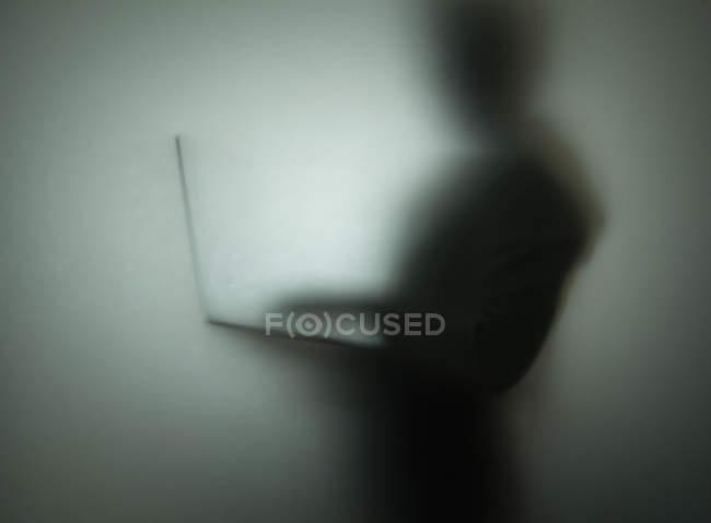 Силуэт человека, использующего ноутбук, за стеклом — стоковое фото