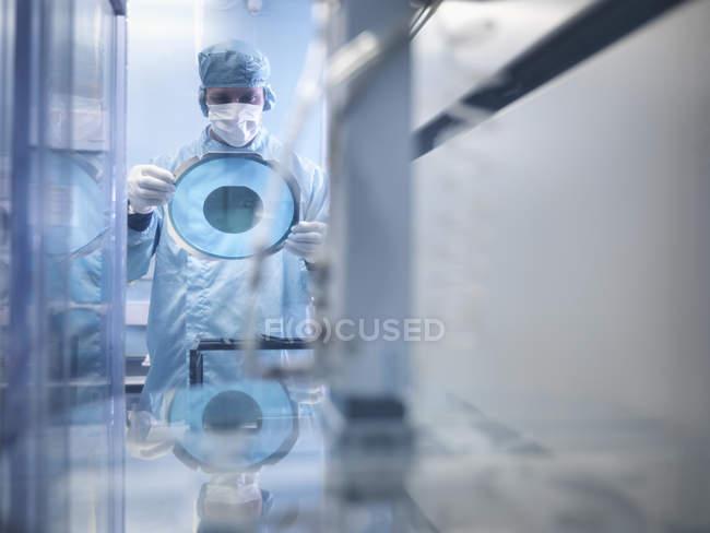 Travailleur d'électronique retenant la plaquette de silicium en coupant la machine dans la pièce propre — Photo de stock