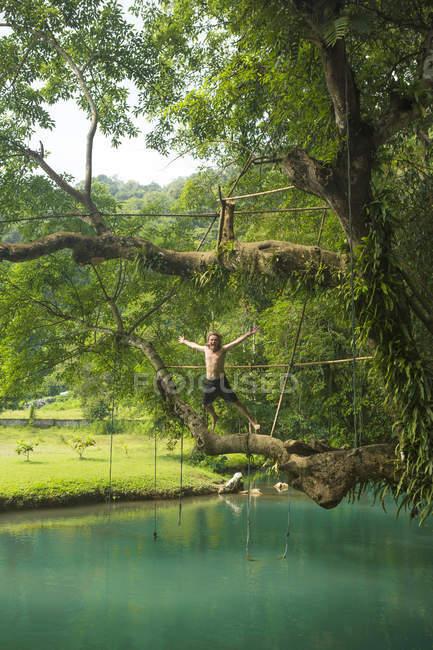 Reifer mann springt mitten in der luft in die türkisfarbene lagune, vang vieng, laos — Stockfoto