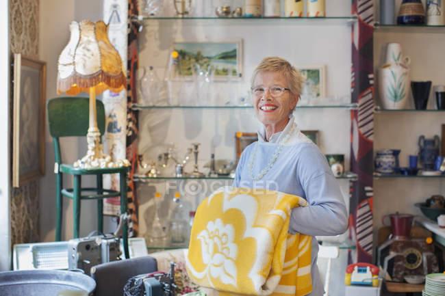 Портрет зрелой женщины, складывающей желтое одеяло в винтажном магазине — стоковое фото