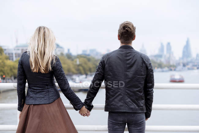 Rear view of romantic young couple in front of Thames river, — Stock Photo