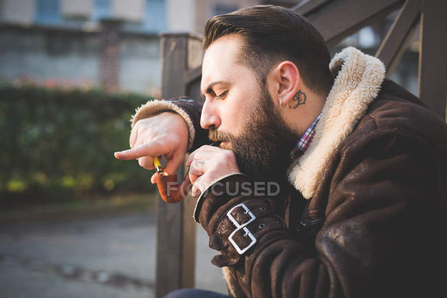 Young bearded man smoking pipe on steps — Stock Photo