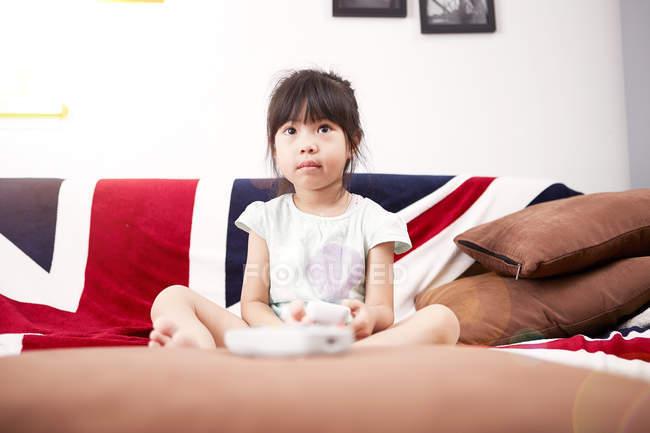 Giovane ragazza seduta sul divano a guardare la televisione a casa — Foto stock