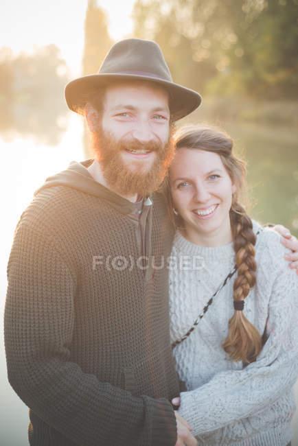 Junges Paar am Fluss sitzend, Porträt — Stockfoto