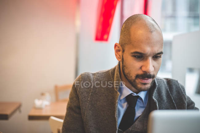 Businessman sitting in cafe using laptop — Stock Photo