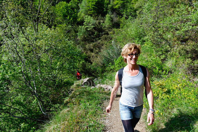 Mature female hiker hiking up hillside path — Stock Photo