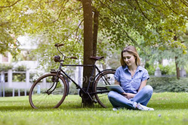 Jovem mulher sentado cruz legged na grama ao lado de bicicleta usando tablet digital — Fotografia de Stock