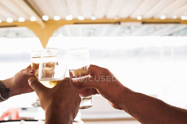 Three male and female hands making a toast with white wine — Stock Photo