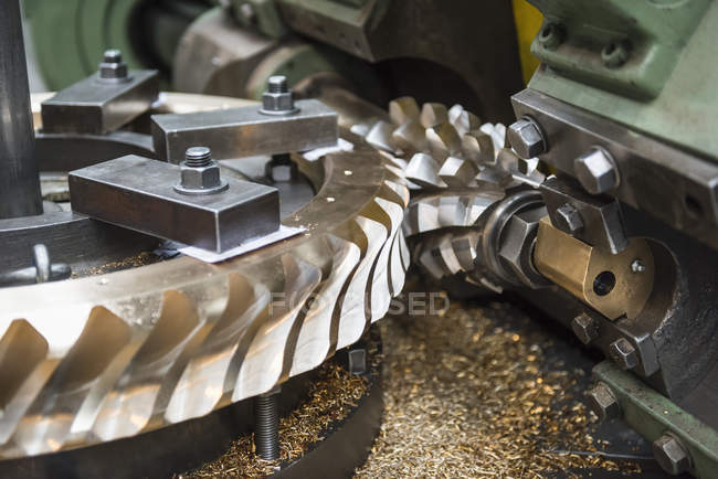 Bronze worm gear with specialist cutting tool in lathe in engineering factory, close up — Stock Photo