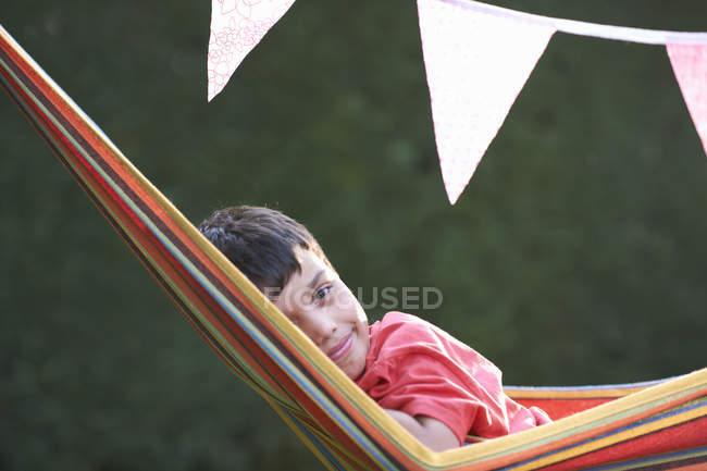 Portrait of cute boy reclining in striped garden hammock — Stock Photo