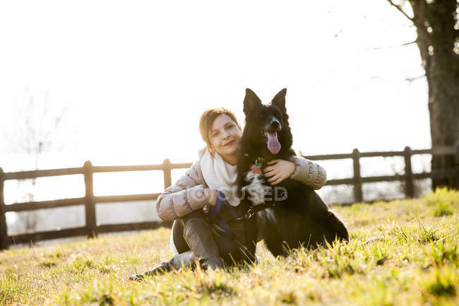Portrait of mid adult woman sitting with her dog in field — Stock Photo