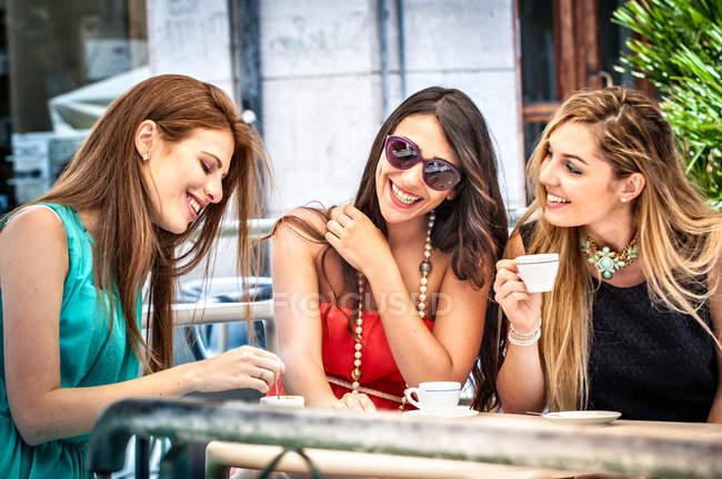 Tres jóvenes amigas bebiendo espresso en el café de la acera, Cagliari, Cerdeña, Italia - foto de stock