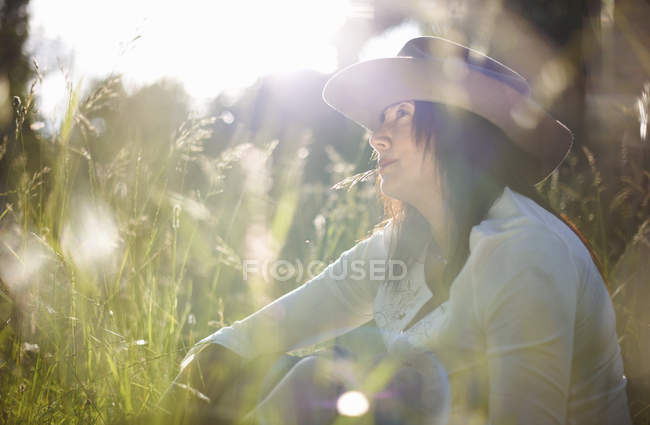Mature woman in cowboy hat with blade of grass in her mouth — Stock Photo