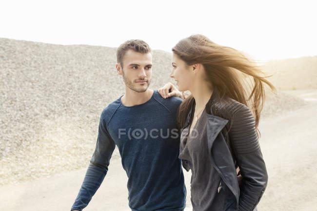 Attrayant romantique jeune couple flânant par gravier colline — Photo de stock