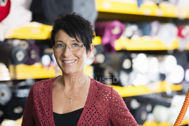 Retrato da costureira madura na frente das prateleiras de matéria têxtil na oficina — Fotografia de Stock