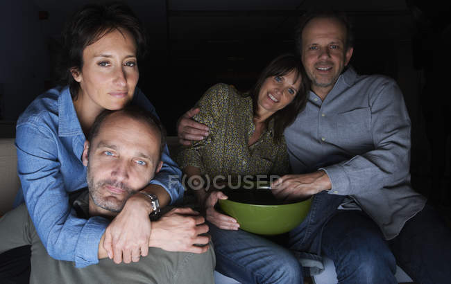 Two mature couples watching TV with snack bowl — Stock Photo
