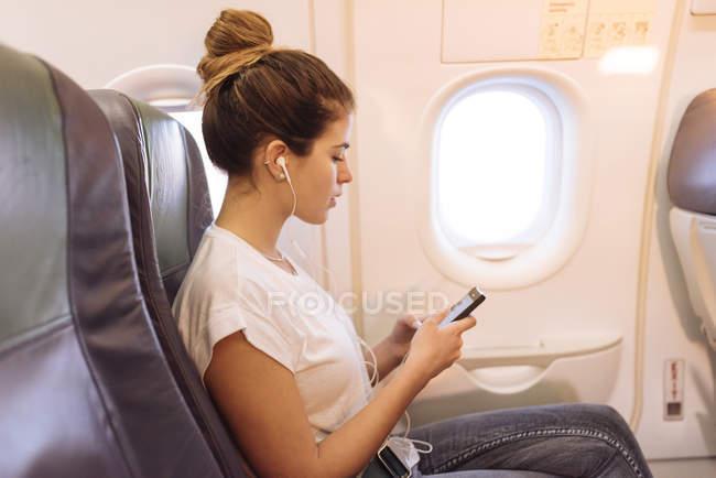 Giovane donna in aereo che sceglie la musica su smartphone — Foto stock
