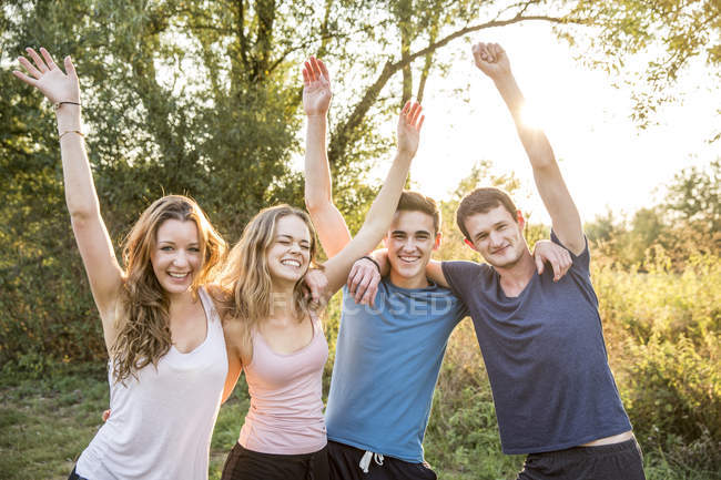 Portrait of group of friends in rural environment, arms raised, smiling — Stock Photo