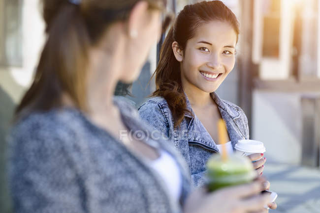 Two young women with takeaway coffee leaning against park building — Stock Photo