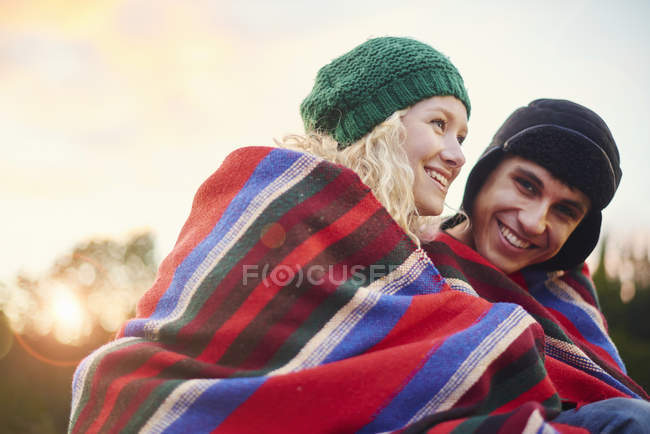 Портрет романтической молодой пары, завернутой в одеяло — стоковое фото