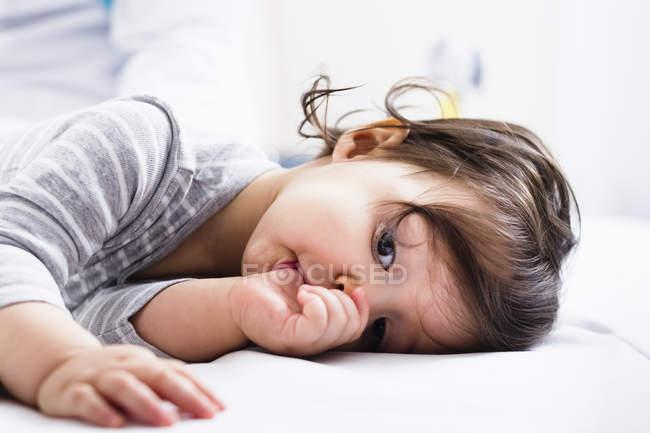 Bambino sdraiato, succhiare pollice — Foto stock