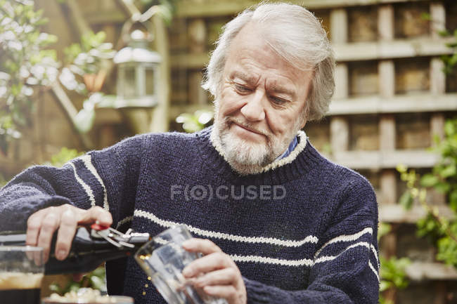 Uomo anziano versando birra — Foto stock