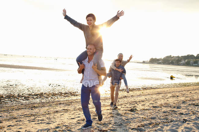 Uomini che danno cavalcata alle donne sulla spiaggia — Foto stock