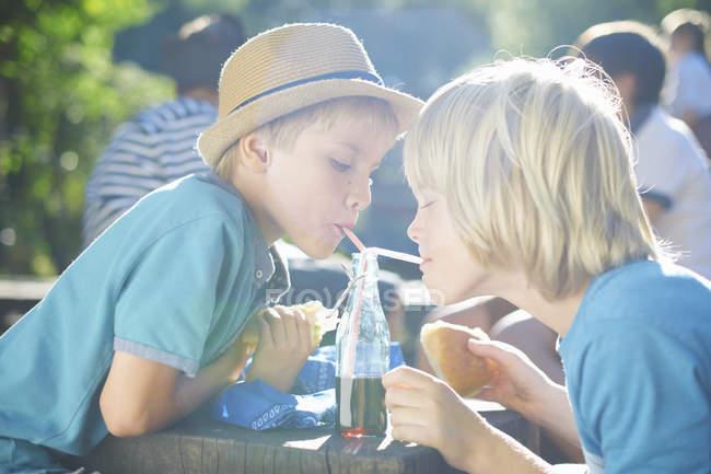 Due ragazzini che bevono dalla bottiglia con le cannucce — Foto stock