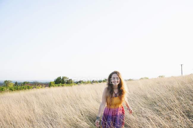 Портрет взрослой женщины, одетой в хиппи, идущей по полю — стоковое фото