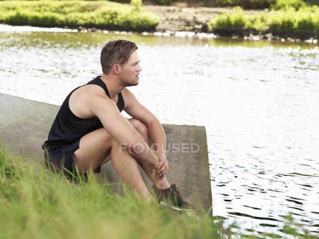 Giovane nello sport seduto sulla riva del fiume — Foto stock