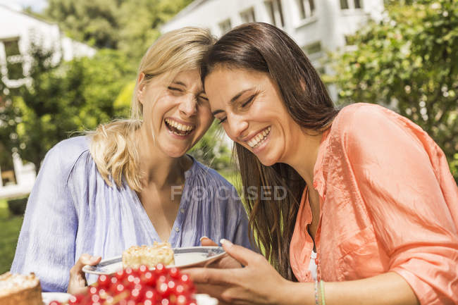 Two female friends in garden, laughing, holding plate with dessert — Stock Photo