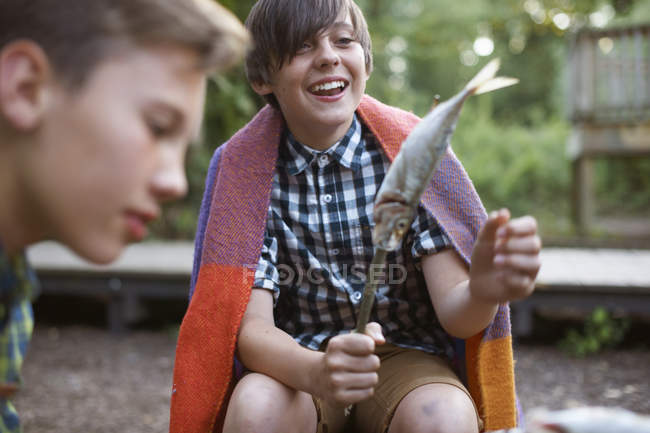 Little boy holding stick with fish on ready to barbecue — Stock Photo