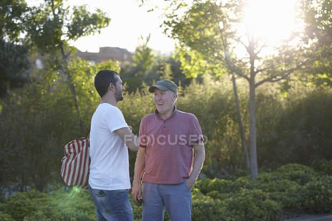 Mid adult man talking to senior man in park — Stock Photo