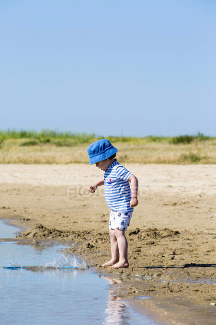 Small boy on beach throwing sand into sea, Marennes, Charente-Maritime, France — Stock Photo